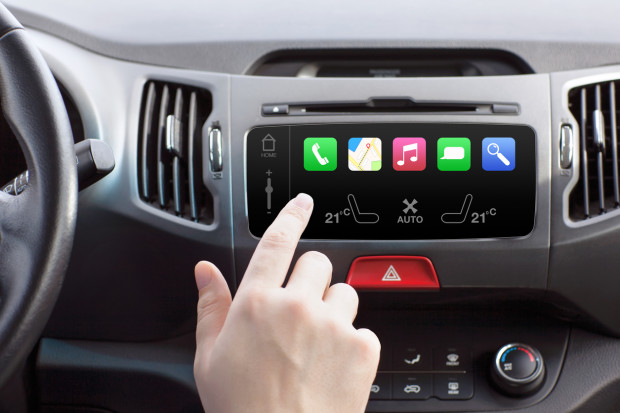 man sitting in a car and touch play finger in a auto smart system